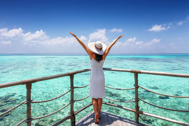Tropical travel concept: happy female traveler in white dress enjoys the view to the turquoise sea Sky Standing Sea Water One Person Leisure Activity Horizon Over Water Scenics - Nature Lifestyles Beauty In Nature Railing Women Arms Raised Outdoors Trip Looking At View Real People Tropics Happy Freedom Concept View Vacations Traveler Tourist