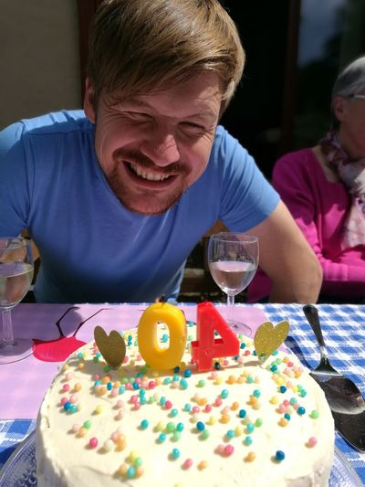 Portrait Of Smiling Mature Man Celebrating Birthday With Mother Sitting In Background