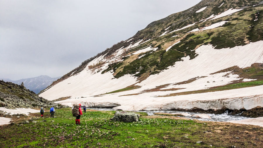 Tourists travel to mountains areas. A group of people is on the route. Beautiful landscape of the valley at the foot of the mountains. Around a lot of greenery, mountain rivers flow, flowers and grass grow. And very close still lies the snow. People are well equipped for long trips and extreme situations. Travel Travel Photography Traveling Activity Beauty In Nature Day Environment Formation Full Length Group Of People Hiking Landscape Leisure Activity Men Mountain Mountain Range Nature Non-urban Scene Outdoors People Real People Scenics - Nature Sky Travel Destinations Water