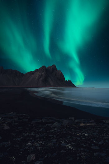 Scenic view of sea by mountains against sky at night