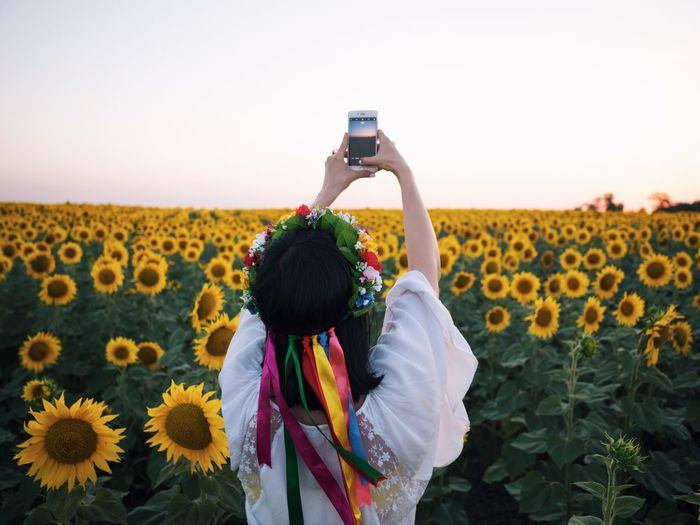 Rear view of woman photographing through mobile phone while standing on field