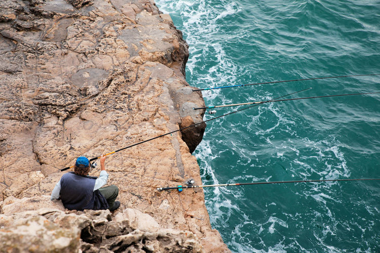 High angle view of man fishing in sea