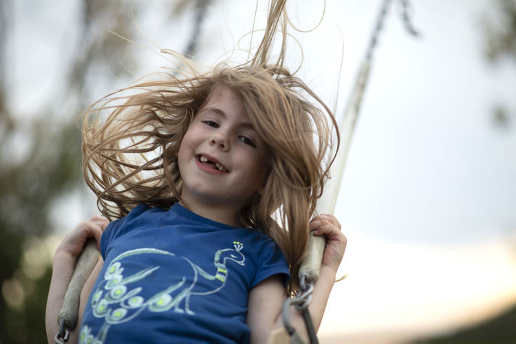 Low angle portrait of smiling girl sitting on swing