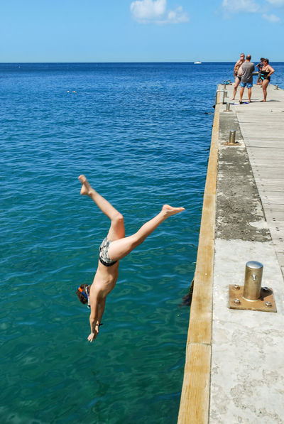 The quay. Diving at Pointe-Noire Martinique, France Blue Blue Sky Children Enjoyment France Jumping Leisure Activity Martinique Ocean Outdoor Outdoors People Pier Q Quay Quiet Quiet Moments Real People Sea Sea And Sky Sky Summertime Vacations Water Waterfront