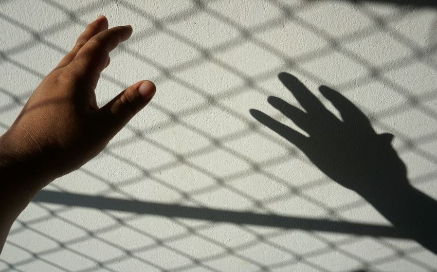 Shadow of person hand on tiled floor