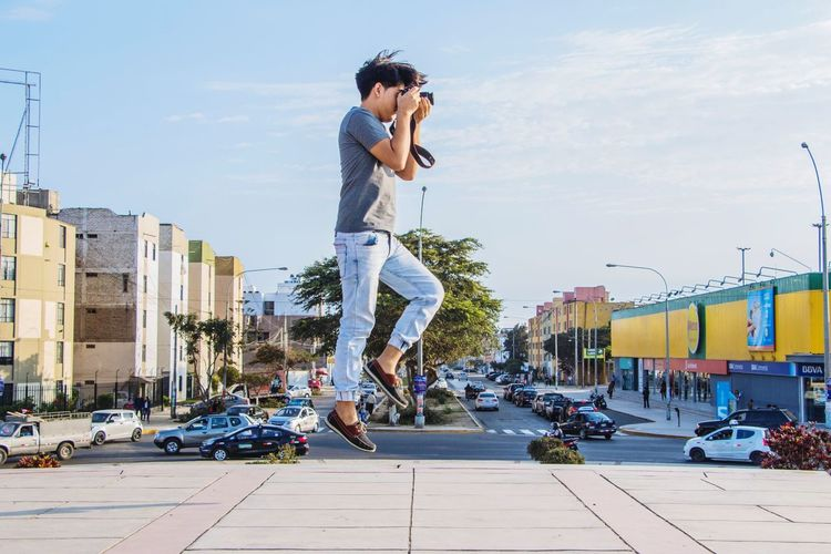 Side View Of Man Photographing While Levitating In City