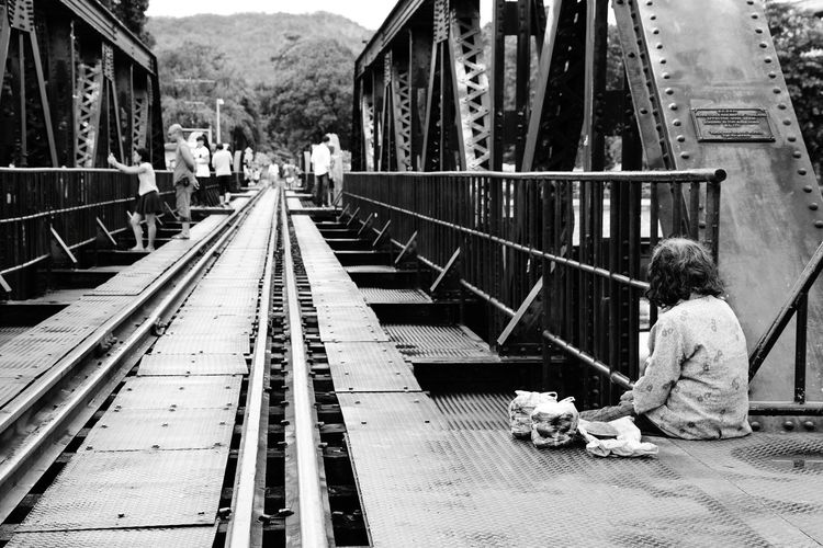 Rear view of female beggar sitting at railway bridge