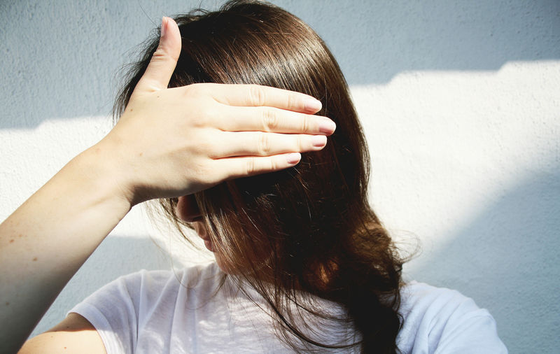 Close-up of woman shielding eyes while standing against wall on sunny day