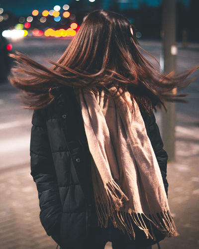 Woman tossing hair while standing in city at night