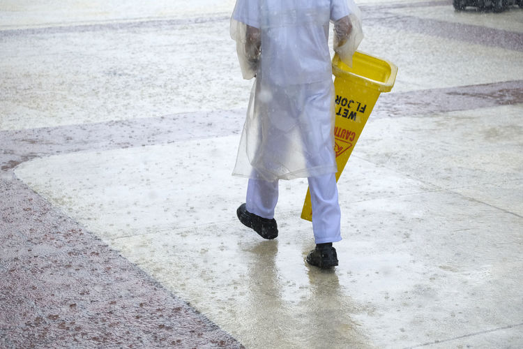 Protection Low Section Security Walking One Person Protective Workwear City Day Human Body Part Standing Clothing Safety Sign Body Part Motion Street Human Leg Occupation Road Outdoors Rain Responsibility Rain Rainy Days Wet Floor The Art Of Street Photography