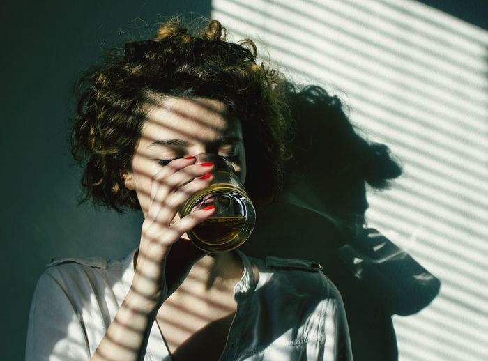 Sunlight falling on young woman drinking alcohol by wall