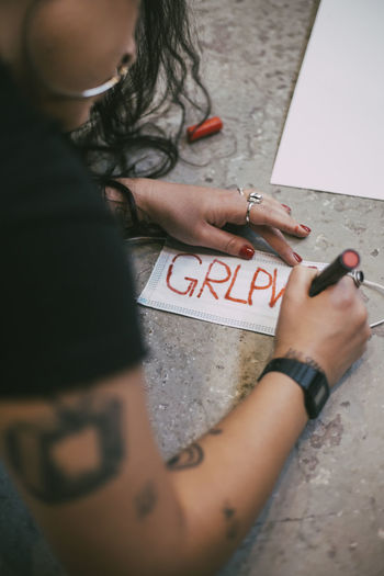 High angle view of woman hand with text