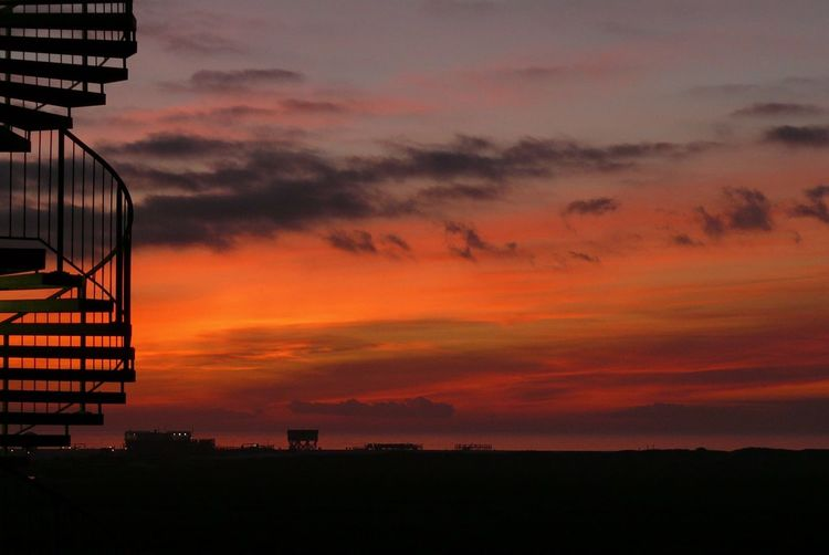 Low Angle View Of Silhouette Landscape Against Orange Sky