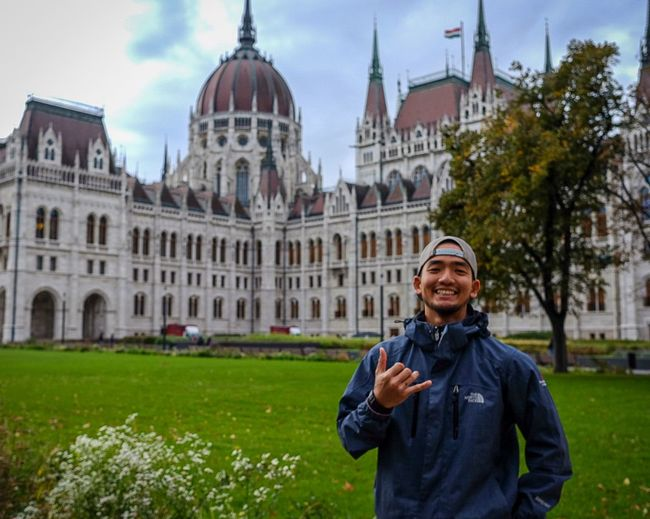 Portrait of smiling man standing against hungarian parliament building