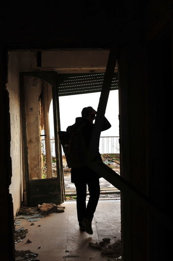 Rear view of silhouette man standing in window