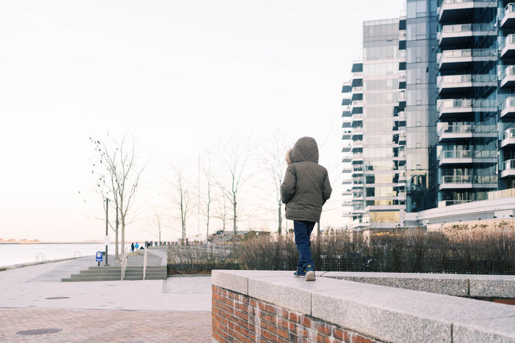 Rear view of woman standing in city against sky