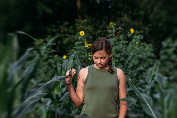 Young woman holding flower while standing against plants