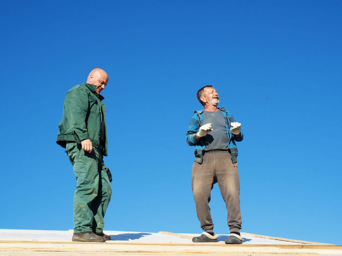 Full length of father and son standing on land against clear blue sky