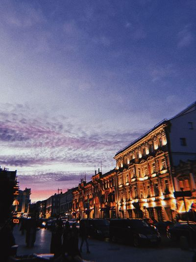 City street and buildings against sky at sunset