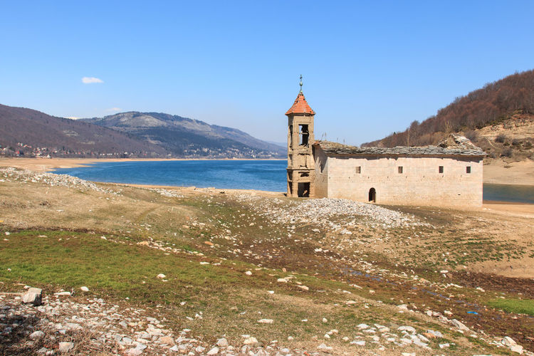 St nicholas church by mavrovo lake against sky