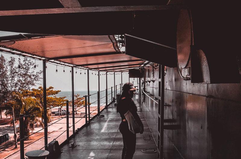 Man photographing woman standing on escalator