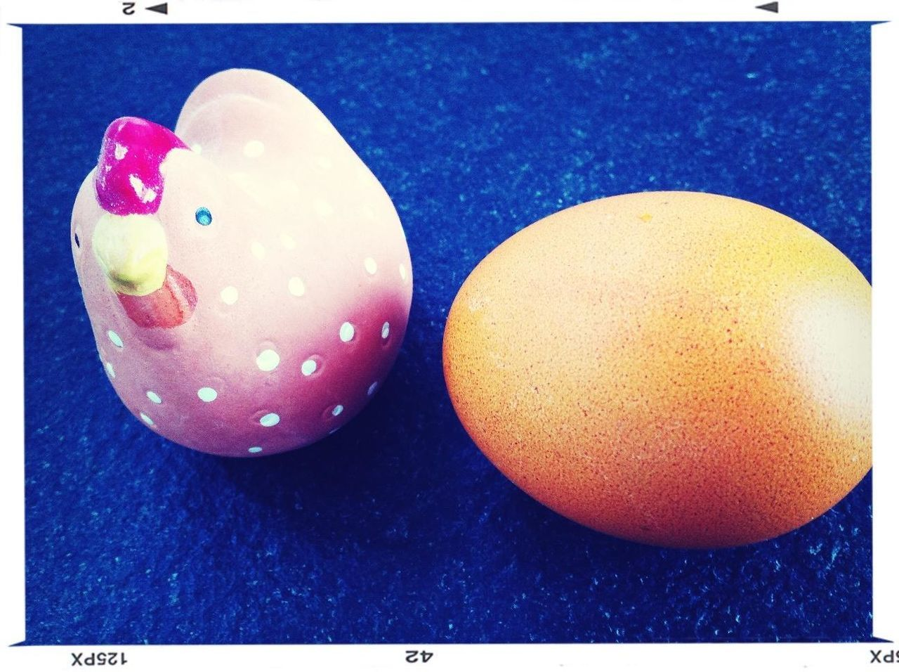 Egg and toy on blue table
