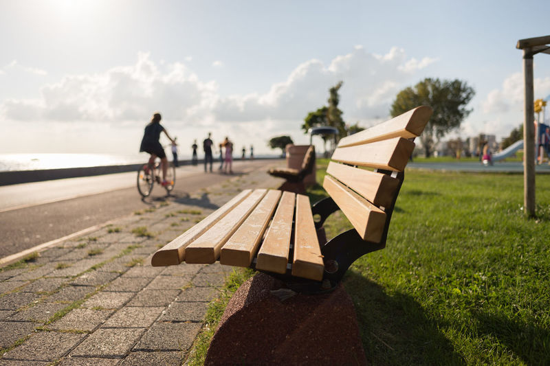 Bench on promenade against sky