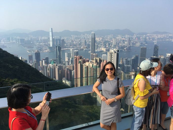 People standing at victoria peak with cityscape in background