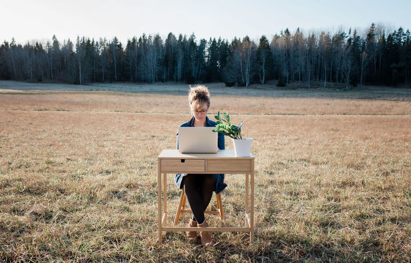 Woman sitting on chair in field