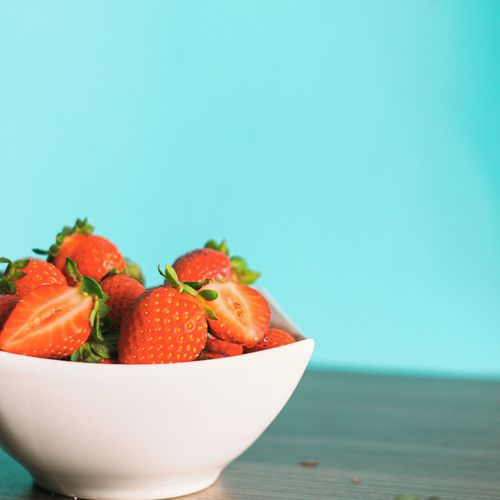 Close-up of fruits in bowl against blue background