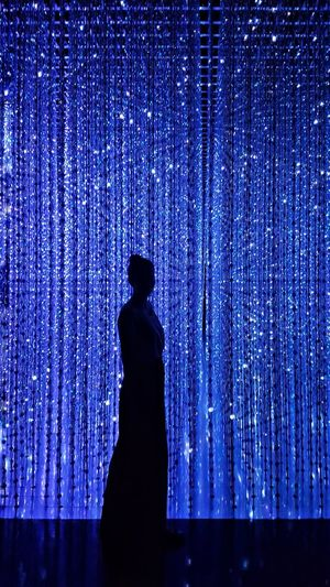 Side view of silhouette woman standing against illuminated curtain