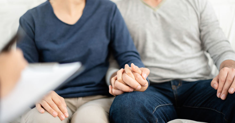Midsection of couple holding hands while sitting on sofa