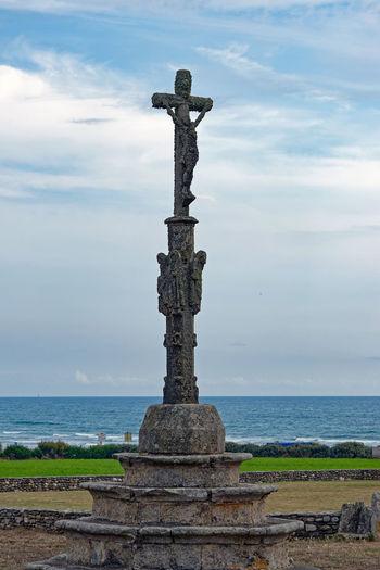 Cross on sea against sky