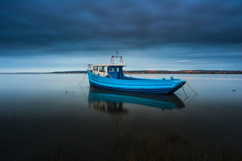 Boat Moored In Sea Against Sky At Dusk