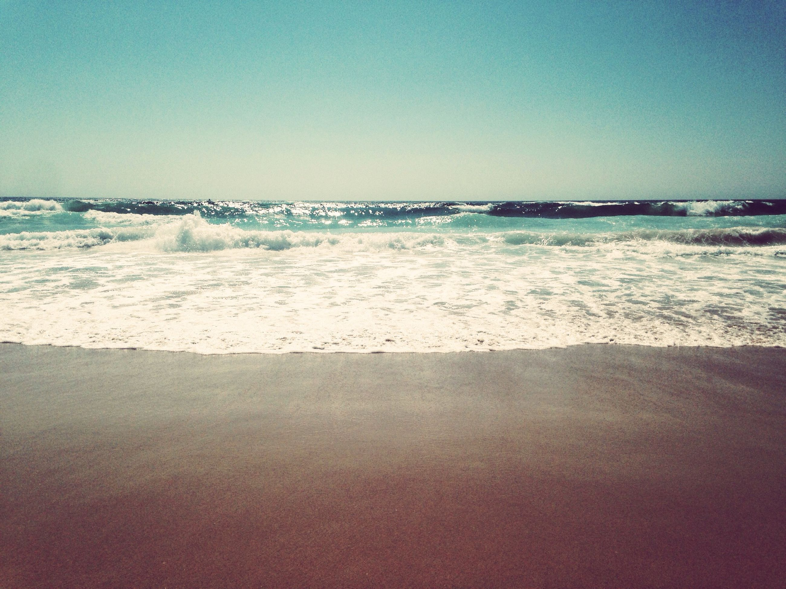 sea, water, clear sky, beach, horizon over water, copy space, wave, shore, scenics, tranquil scene, sand, beauty in nature, tranquility, surf, blue, nature, idyllic, waterfront, motion, outdoors