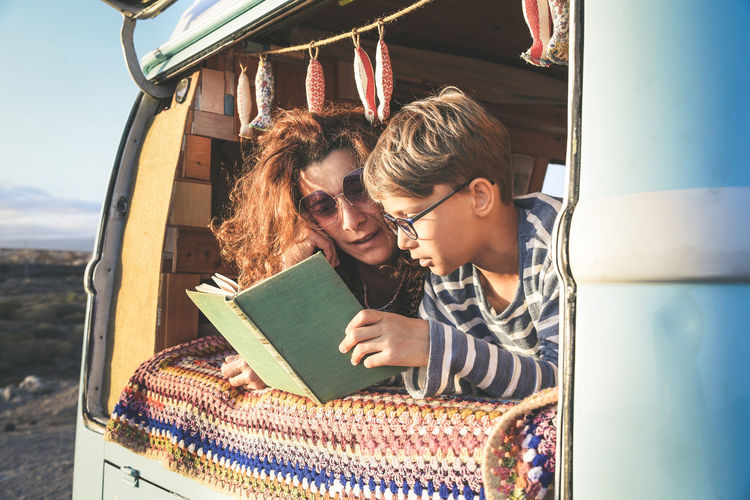 adventure at the sunset, Hipster couple mum and son traveling together on vintage van transport. Life inspiration concept with hippie people on minivan, reading a book together. Warm sunshine Leisure Activity Real People Young Adult Women Young Women Lifestyles Two People Bonding Activity Adult People Young Men Emotion Togetherness Casual Clothing Day Sitting Smiling Portrait Outdoors Positive Emotion Hairstyle