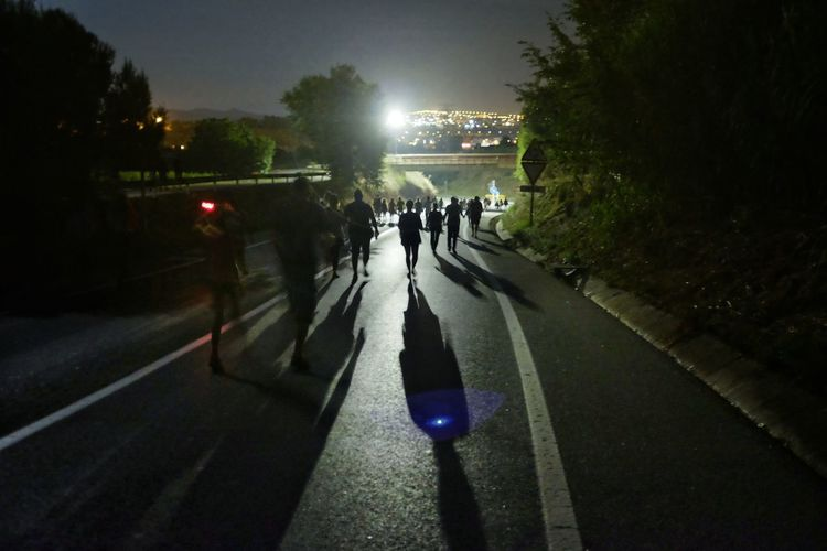 Group of people walking on road at night