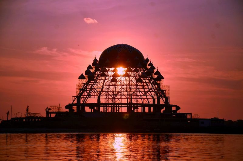 Silhouette built structure by sea against sky during sunset
