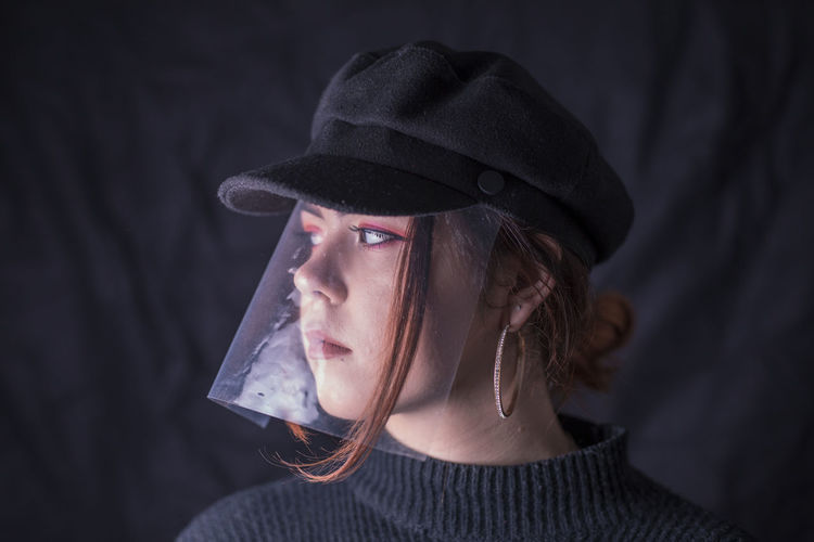 Close-Up Of Young Woman Wearing Cap And Plastic At Home