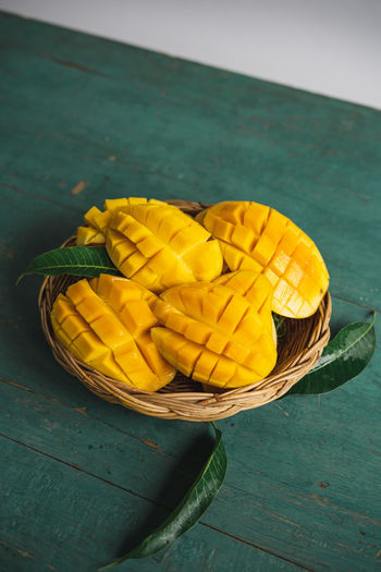 Mango in a basket on a green wood Yellow Food And Drink Freshness Food Healthy Eating Wellbeing Table Still Life Fruit No People Close-up Container Wood - Material Basket High Angle View Day SLICE Banana Nature Outdoors