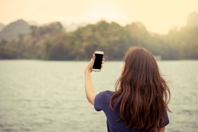 Rear View Of Woman Using Mobile Phone Standing Against Lake