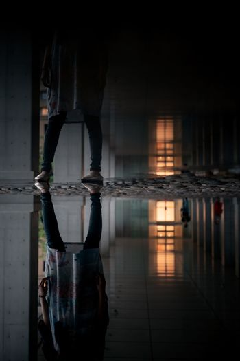Reflection of man and woman standing in water