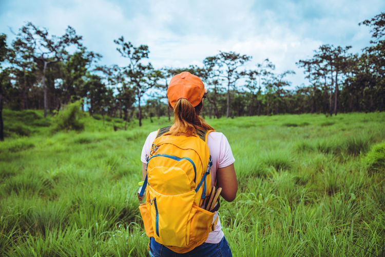 Rear view of woman with backpack standing on grassy land