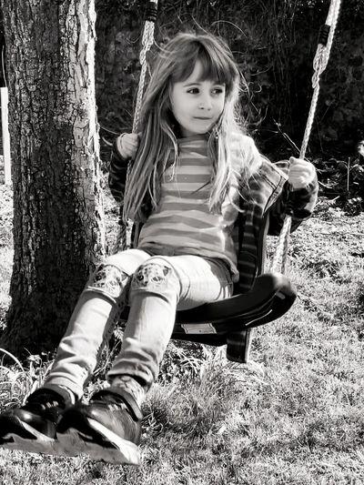 Portrait of girl sitting on tree trunk