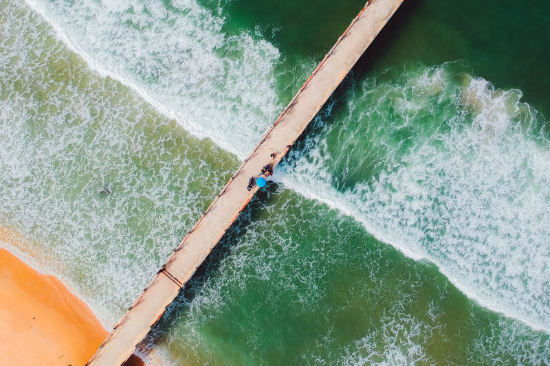 Directly above shot of people on pier over sea