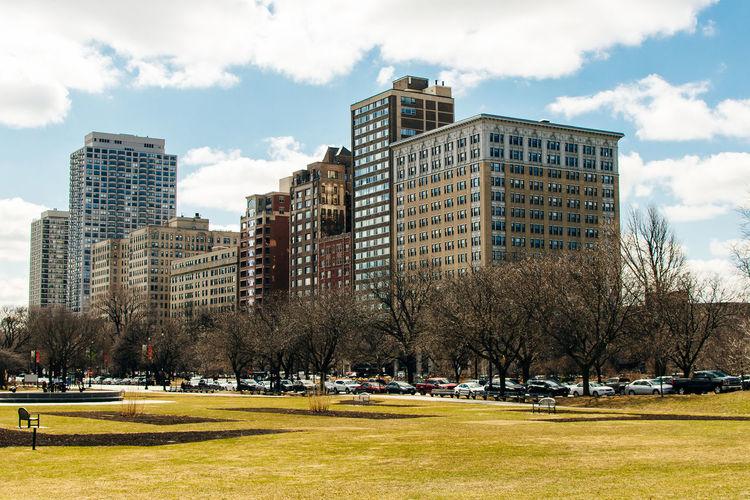 Park by buildings in city against sky