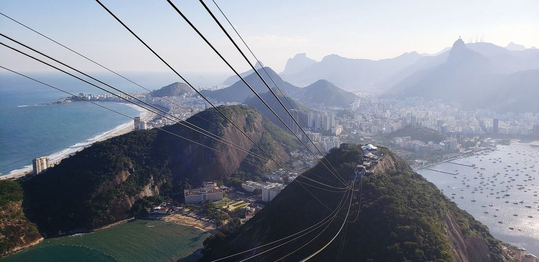 Overhead cable car over sea and mountains against sky