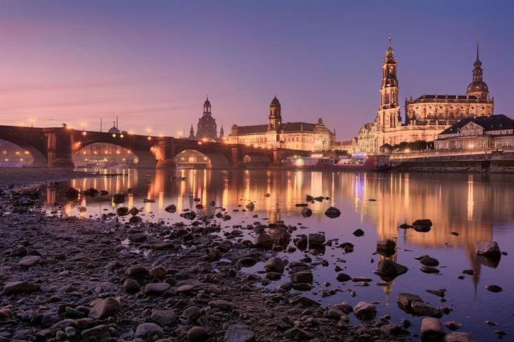 Elbe river against illuminated buildings in city