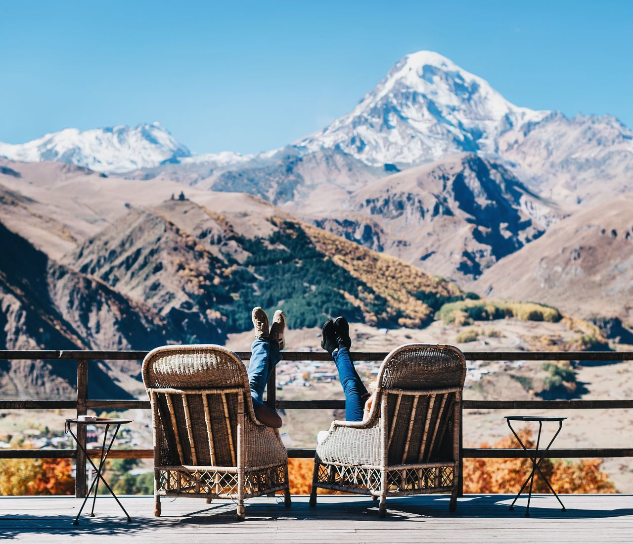 People Relaxing Against Snowcapped Mountain And Clear Blue Sky