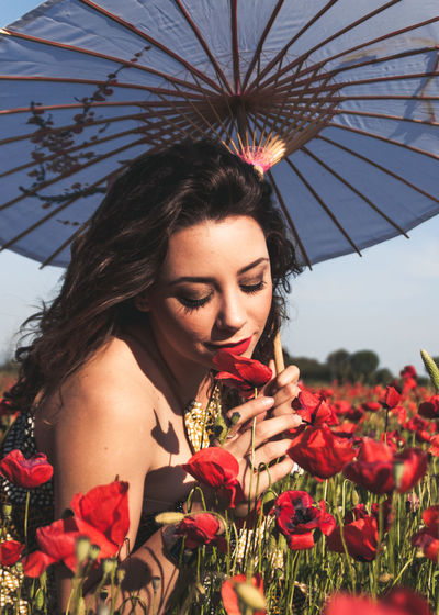 Young Woman With Umbrella Smelling Red Flowers During Sunny Day